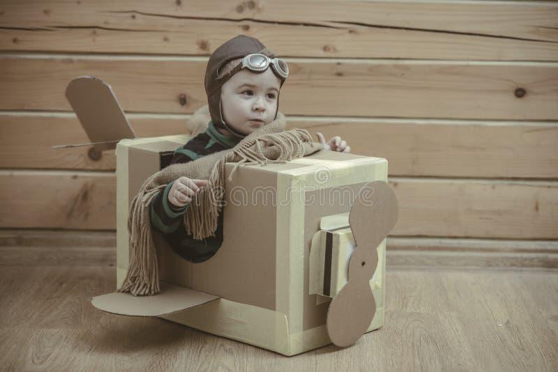 Boy pilot flying in a cardboard box. Small boy pilot flying in a cardboard box stock photo