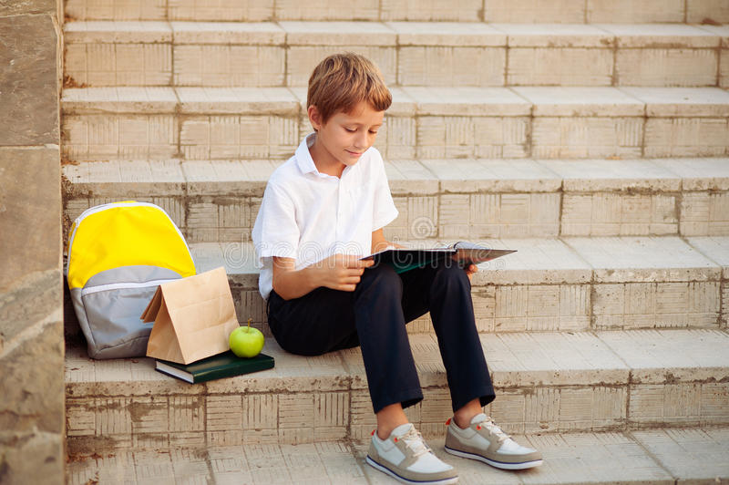 Small boy reading a book On the stairs of the school stock photography