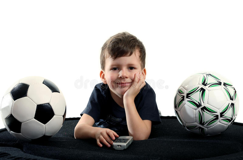 Small boy recreation on sofa with two balls