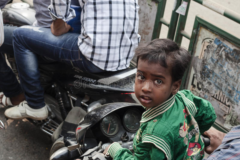 Small boy riding on a bike with family. VARANASI, INDIA - OCTOBER 28: Small boy riding on a bike with family. Motorbike is the most favorite vehicle and most stock photo