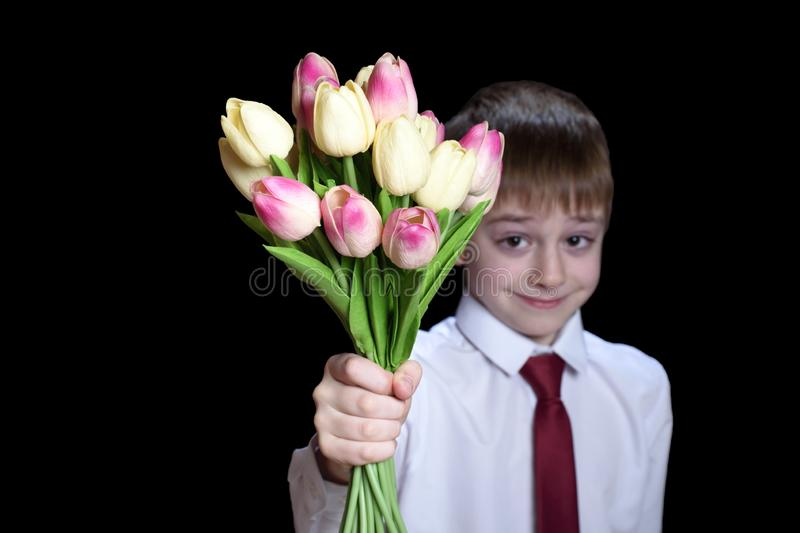 Small boy in a shirt with tie holding a bouquet of tulips. Isolate on black background royalty free stock photo