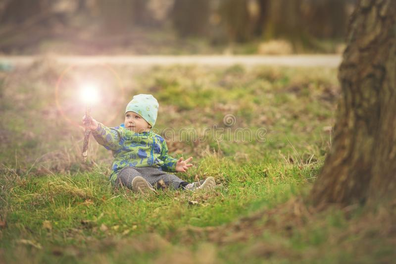 Small boy is sitting on grass and handling magic wand in spring park near big tree royalty free stock photo