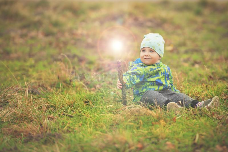 Small boy is sitting on grass and holding magic wand with light out of it royalty free stock photos