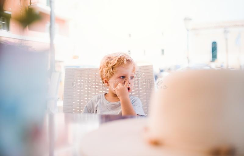 Small boy sitting in outdoor restaurant on summer holiday, picking nose. A small boy sitting in outdoor restaurant on summer holiday, picking nose royalty free stock photography