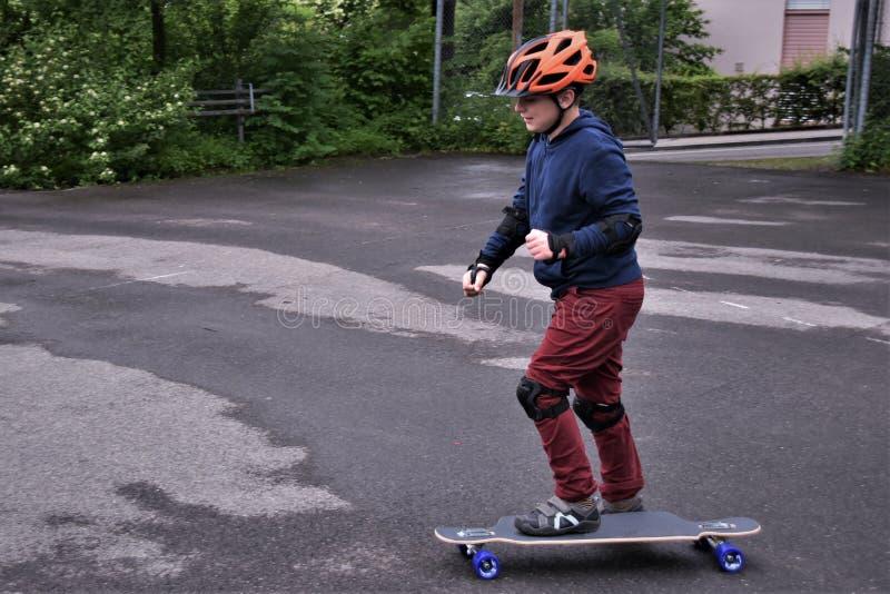 A small boy skateboarding on an asphalt sport ground stock photography