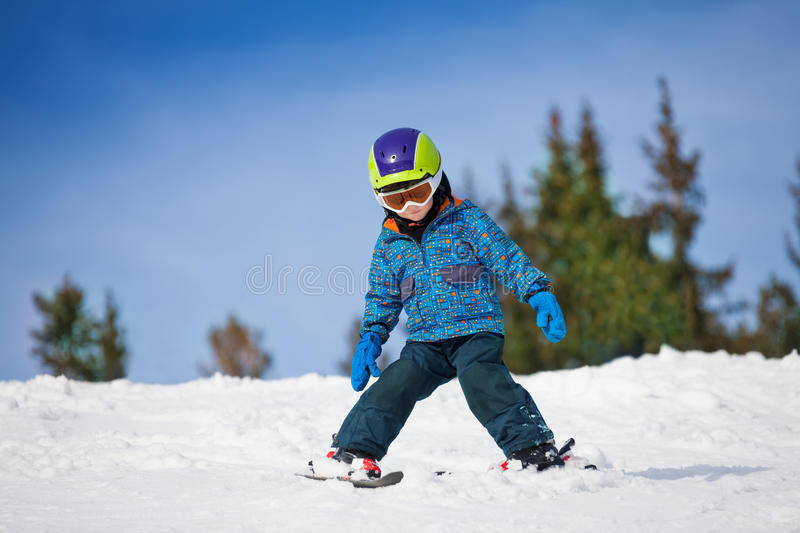 Small boy in ski mask and helmet learns skiing. Down the hill with legs sliding in different directions stock photo