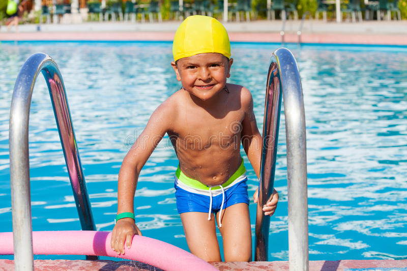 Small boy standing with pool noodle holding ladder. Happy small boy standing with pool noodle holding ladder in swimming pool during summer royalty free stock photos