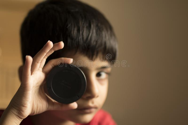 A small boy trying to focus through a lens cap. An artistic portrait of a small boy, who is looking at a lens cap with high concentration royalty free stock images