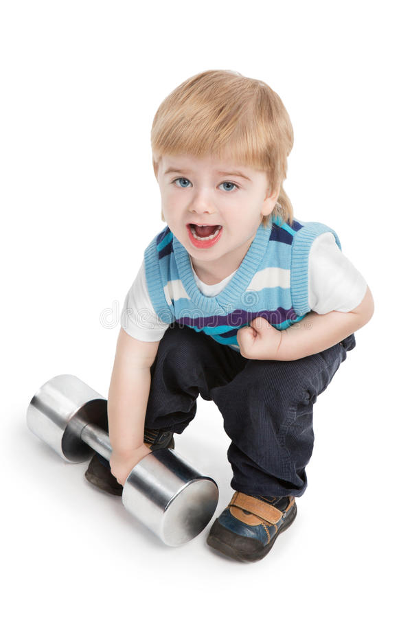 Small boy is trying to raise large dumbbell. Young champion on white background stock photo
