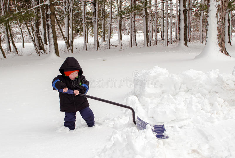 Small boy trying to shovel snow. A small toddler boy tries to shovel snow with a shovel that is bigger than he is. not so easy stock photos