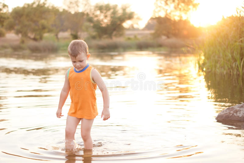 Small boy wading in a lake at sunrise royalty free stock images