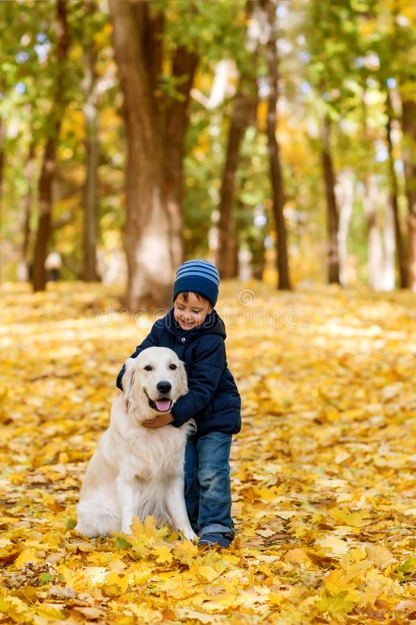 A small boy wearing jeans and a blue jacket emotionally embrace stock image
