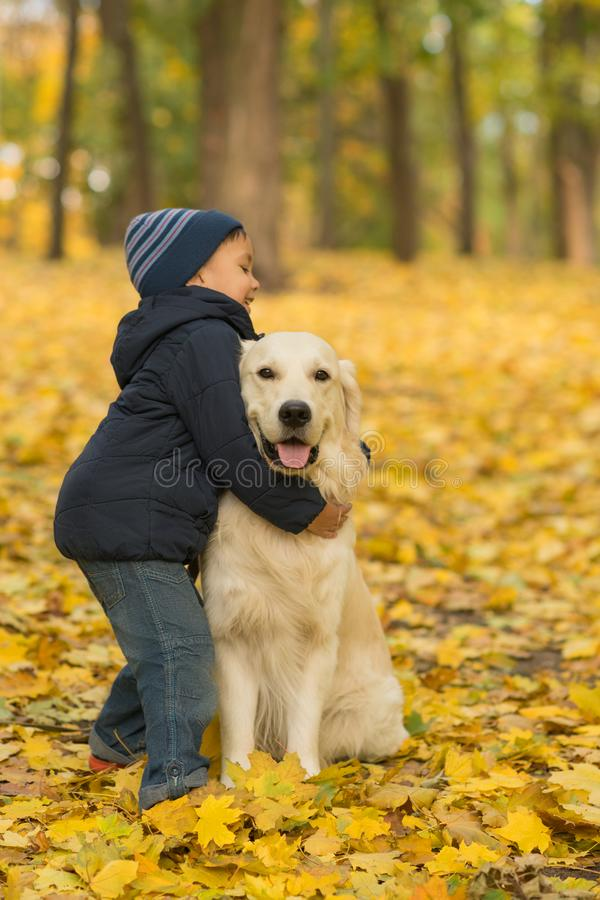 A small boy wearing jeans and blue jacket emotionally embraces royalty free stock image