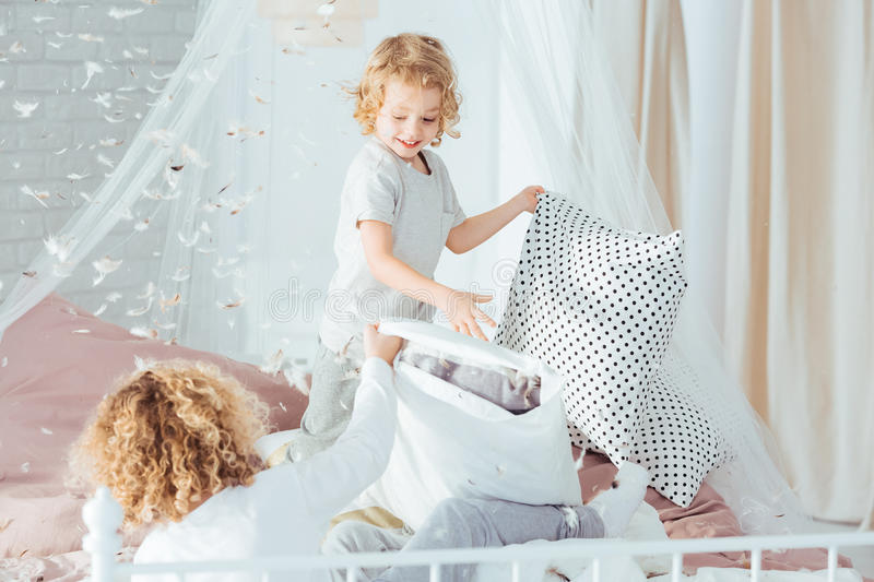 Small boys having pillow fight. Doing mess in room stock photos