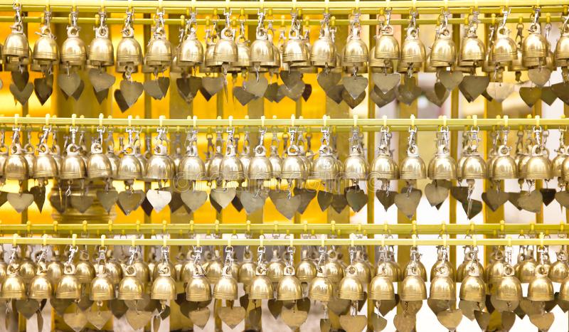 Small brass  praying bells  big group hanging in steel line patterns at  Phra That Hariphunchai temple in Lamphun , Thailand. Close up Small brass  praying bells stock images