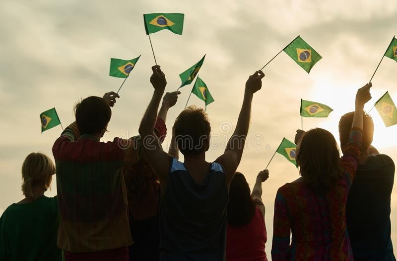 Small brazilian flags. Small brazilian flags in people hands. Back view. Evening sky bakground stock photo