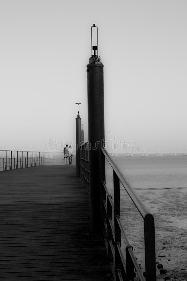 Small bridge on the river in black and white with couple stock photo