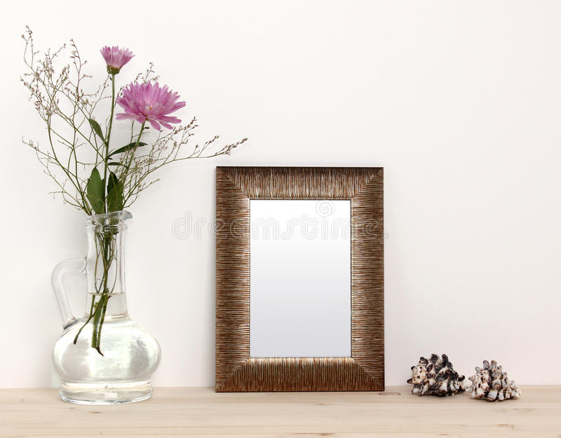 Small bronze frame mockup. With flowers and sea shells royalty free stock image