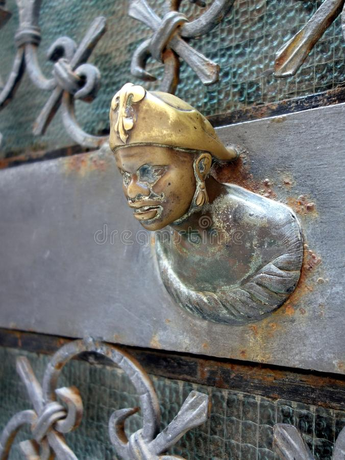 Small Bronze Military Figure, Venice, Italy. Small brass figurine in sailor or military beret, cap, mounted on metal gate, grill, Venice, Italy stock image