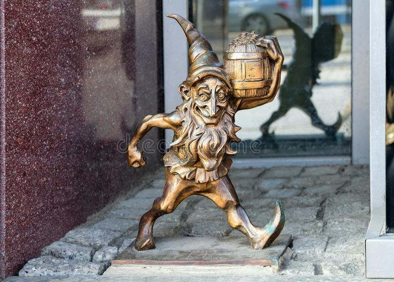 The small bronze statue gnome by name - Leprokonus, gnome with a barrel of gold stock images