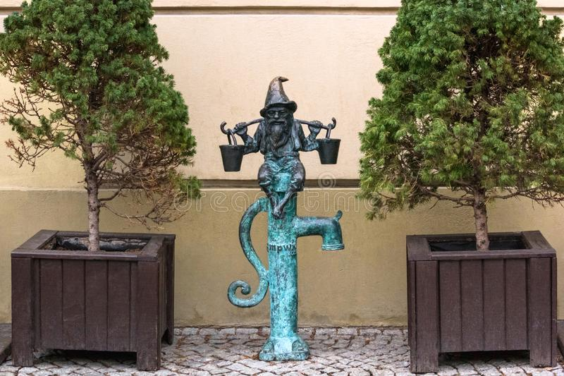 The small bronze statue gnome by name - Wodziarz, gnome with buckets on water column. On the streets of Wroclaw, Poland, January 15, 2018 royalty free stock photos
