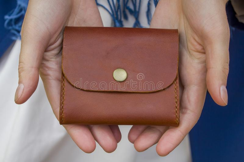 Small brown stitched wallet in female hands close-up on a white skirt with a blue scarf royalty free stock photography