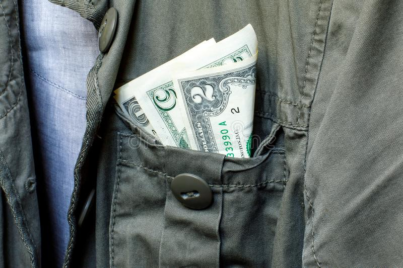 Small bucks in the pocket of a green work jacket. The concept of earning, saving or spending money. Monetary concept. Close-up stock image
