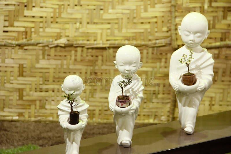 Small Buddha statues holding Bonsai Trees, Bonsai tree exhibition at Pune. stock image