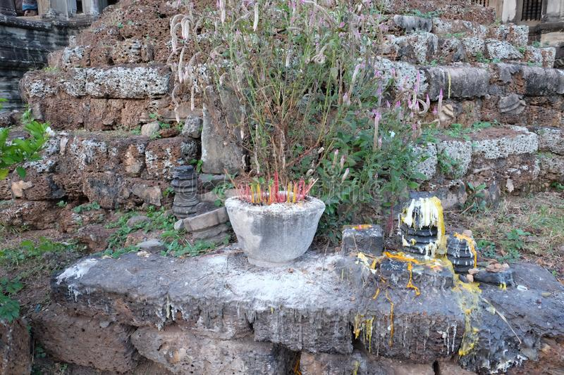 A small Buddhist altar with lots of incense sticks. Frozen melted wax streams.  stock images