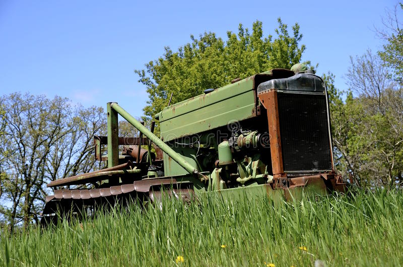 Small bulldozer parked in the long grass. A small bulldozer exposing one rusty track in the grass gives evidence of little usage stock image