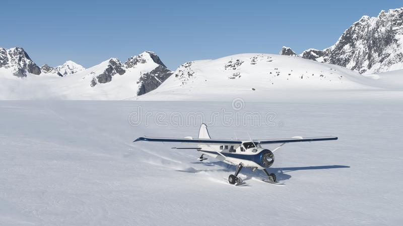 Small plane landing on snow in Alaskan mountains royalty free stock photography