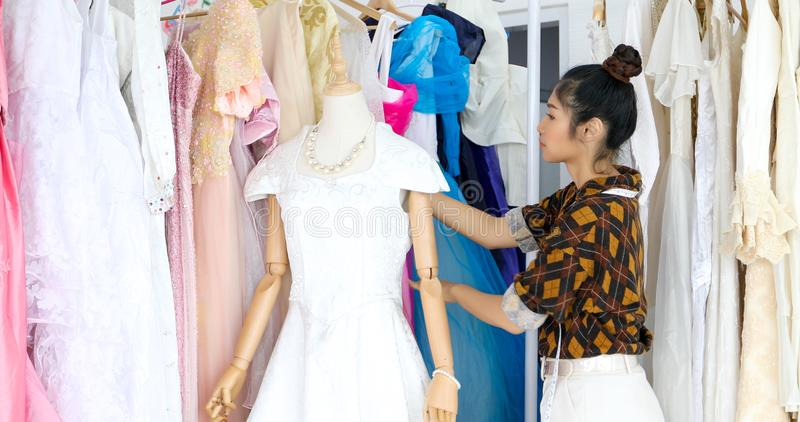 Small Business of Asian women Fashion Designer Working and using smart phone and tablet With Wedding Dresses at at clothing store stock images