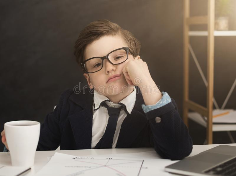 Small business boy got bored in office. Boring job. Small business boy got bored at work, sitting at table. Little boss in office, copy space stock image