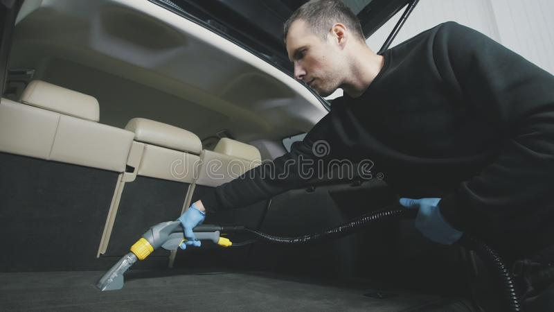 Small business - cleaning of vehicle wardrobe with vacuum cleaner royalty free stock images