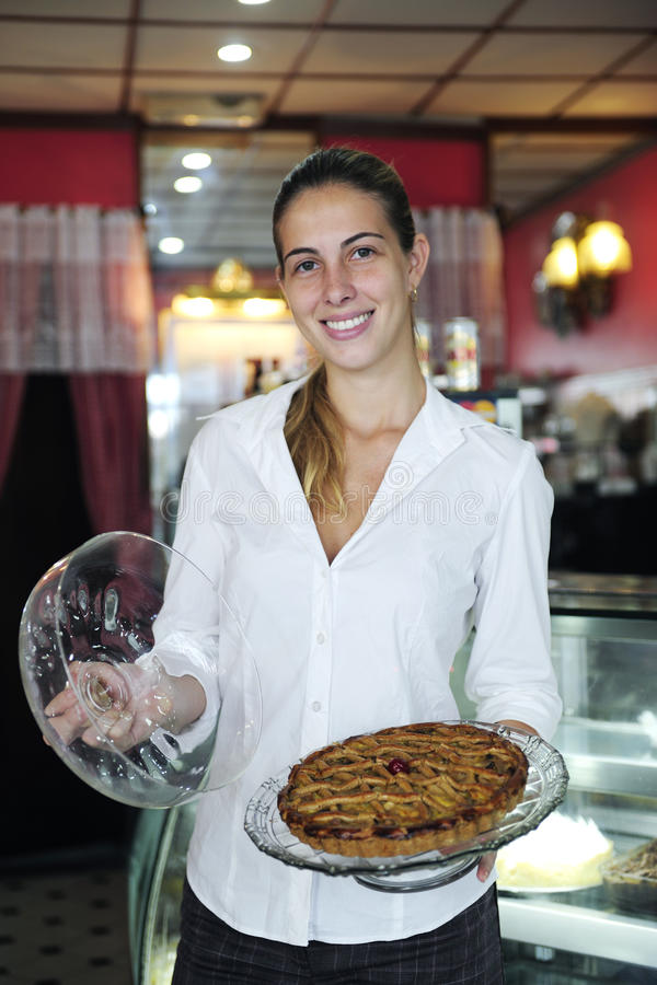 Small business: female owner of a cafe. Small business: proud female owner of a cafe showing a cake stock photo