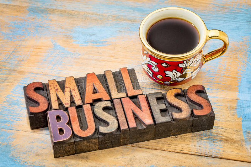 Small business in letterpress wood type. Small business - text in vintage letterpress wood type printing blocks with a cup of coffee royalty free stock photo