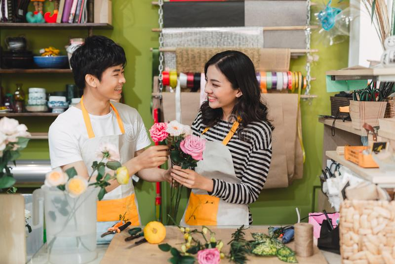 Small business. Male and female florists making rose bouquet in flower shop. Man owner and woman assistant in floral design studio royalty free stock image
