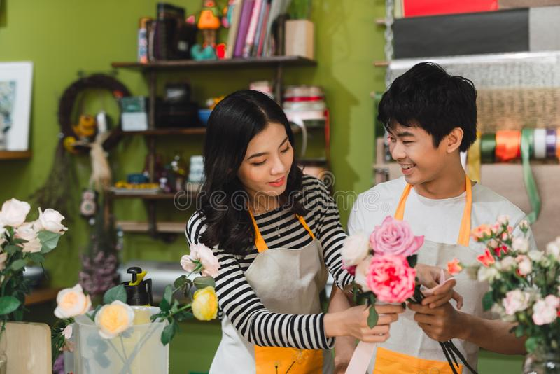 Small business. Male and female florists making rose bouquet in flower shop. Man owner and woman assistant in floral design studio stock photos