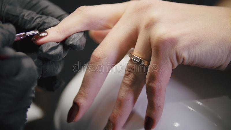 Small business - manicurist - nail master in medical mask doing professional manicure stock photography