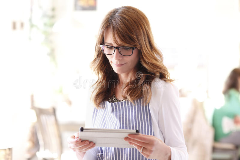 Small business owner. Small business bakery shop owner holding tablet in hands royalty free stock photo