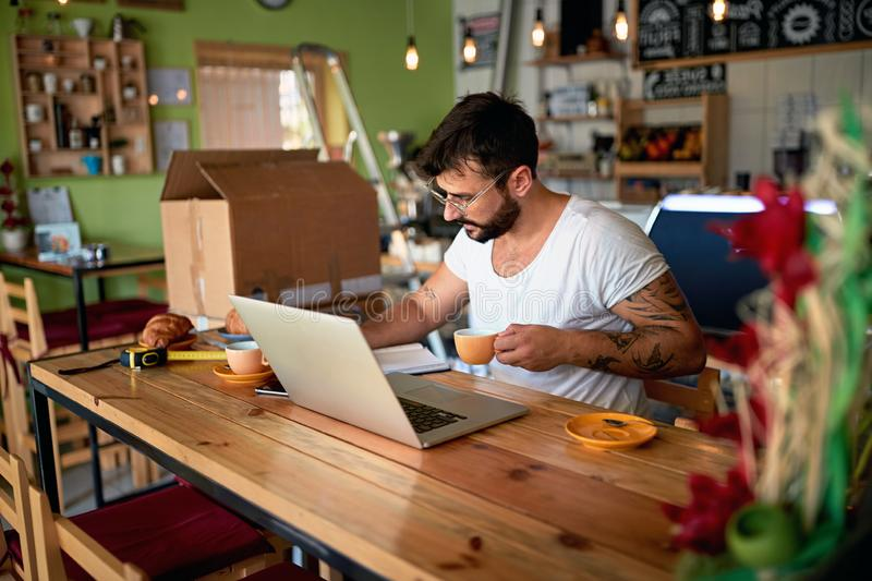 Business owner in coffee shop working on laptop. Small business owner in coffee shop working on laptop royalty free stock photography