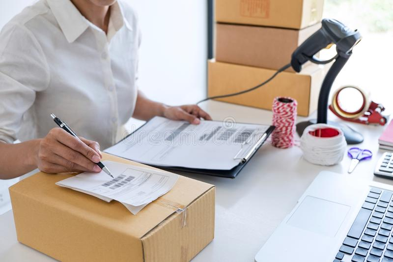 Small business owner delivery service and working packing box, business owner working checking order to confirm before sending. Customer in post office stock photography