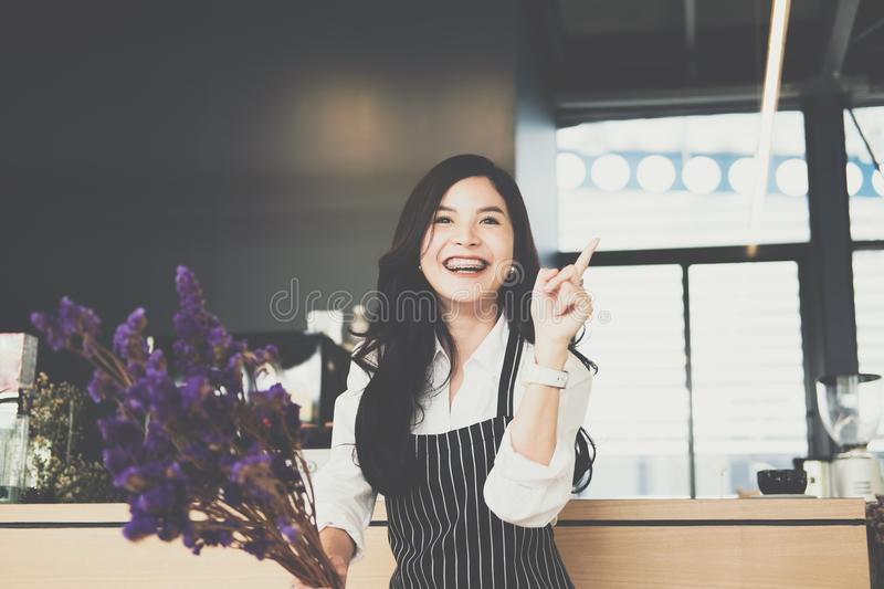 Small business owner holding purple flower at counter in coffee royalty free stock photo