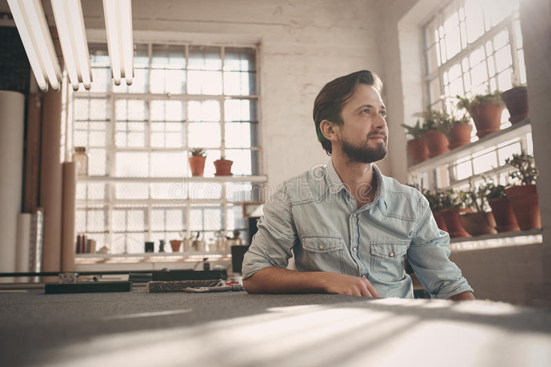 Small business owner looking away thoughfully in his studio royalty free stock photos