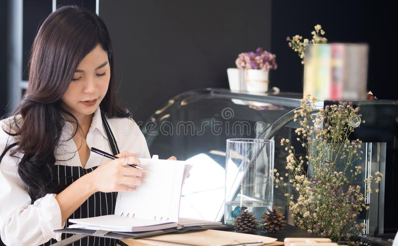 Small business owner with notebook at counter in coffee shop. fe stock photography