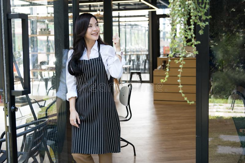 small business owner standing at coffee shop. female barista wearing apron smiling at cafe. food service, restaurant concept. royalty free stock photo