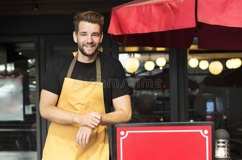 Small business owner standing in front of restaurant stock images