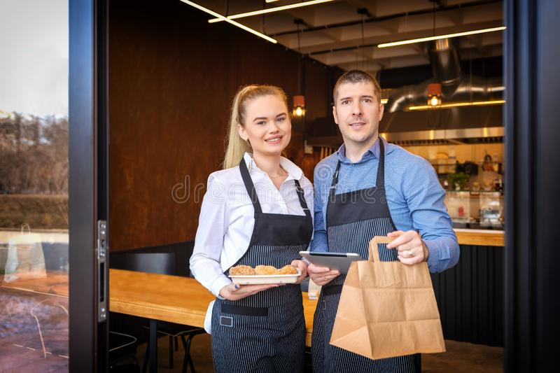 Small business owners couple standing in doorway of trendy restaurant delivering takeaway orders and attending customers stock photos
