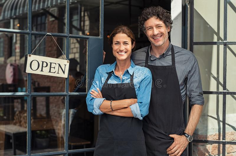 Small business owners couple. Two cheerful small business owners smiling and looking at camera while standing at entrance door. Happy mature men and mid women at royalty free stock photos