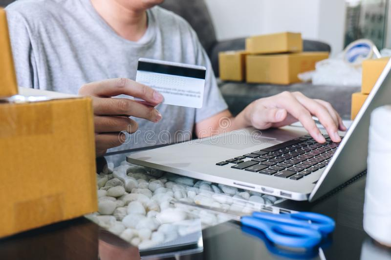 Small business parcel for shipment to client, Young man received online shopping parcel opening boxes and buying items by credit. Card, online marketing on stock image